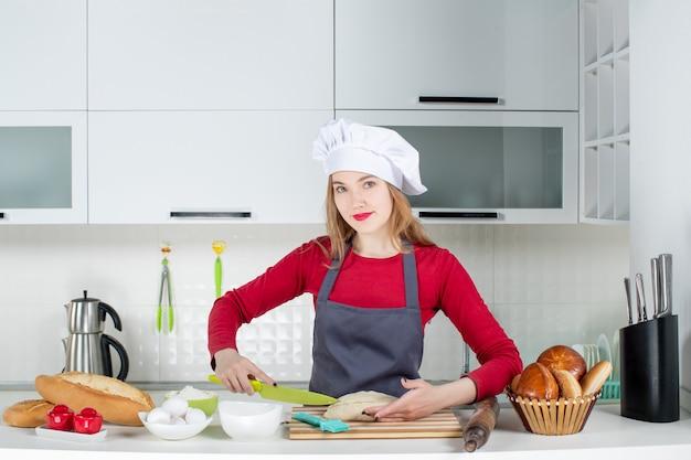 Vista frontale bella donna con cappello da cuoco e grembiule che taglia pane in cucina moderna