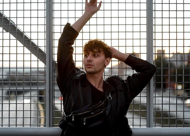 Вид спереди небинарный человек позирует на металлическом заборе