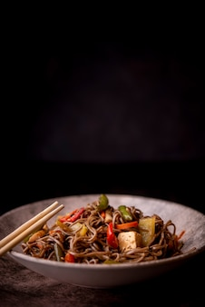 Front view of noodles in bowl with vegetables