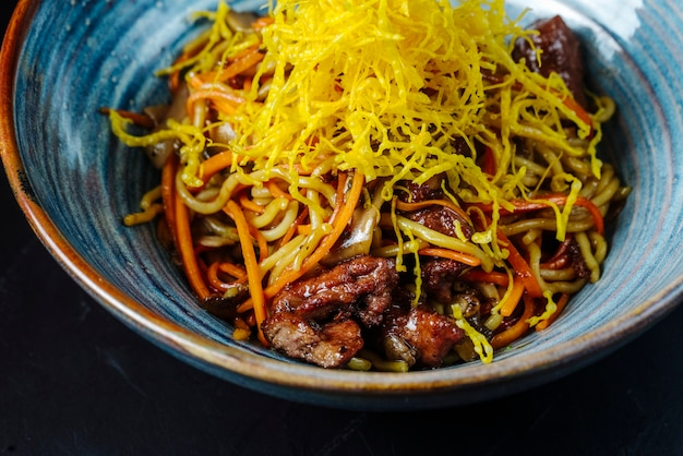 Front view noodles with fried vegetables and meat with grated cheese in a bowl