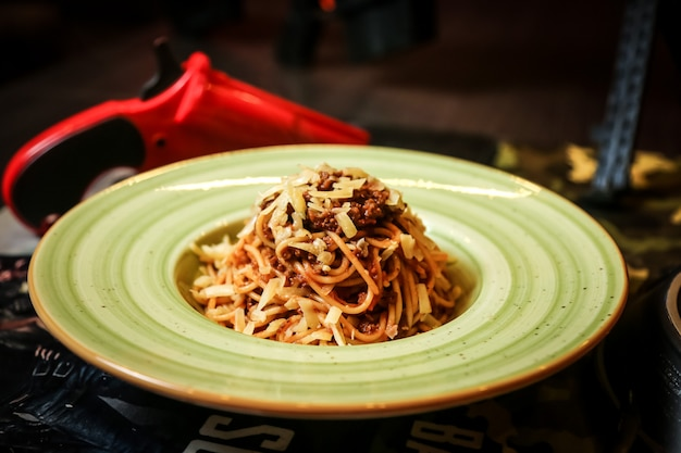 Front view noodles with meat and grated cheese in a plate