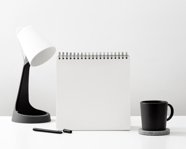 Front view of notebook on desk with mug and lamp