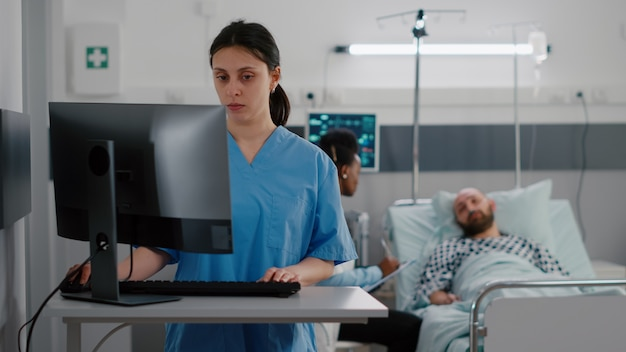 Front view of nurse typing medical expertise on computer while in background black practitioner doctor discussing with sick man healthcare treatment. hospitalized patient having respiratory disorder