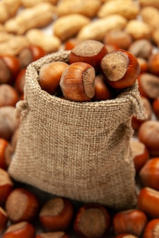 Nocciole e arachidi fresche della composizione del dado di vista frontale sulla noce di arachidi dello snack del dado della scrivania bianca