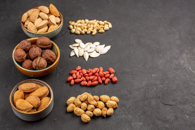 Front view of nut composition with different fresh nuts on dark surface