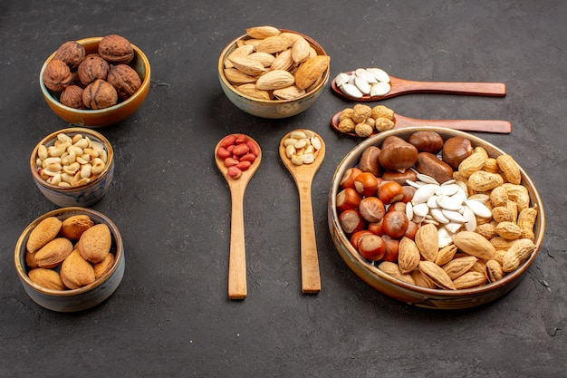 Front view of nut composition with different nuts on dark surface