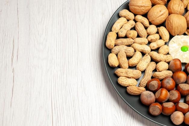 전면 보기 견과류 구성 흰색 책상 너트 나무 스낵 공장 많은 껍질에 접시 안에 신선한 호두 땅콩과 헤이즐넛 무료 사진