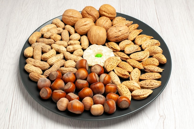 전면 보기 견과류 구성 흰색 책상 너트 나무 스낵 공장 많은 껍질에 접시 안에 신선한 호두 땅콩과 헤이즐넛