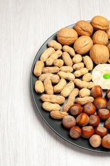 Vista frontale composizione di noci noci fresche arachidi e nocciole all'interno del piatto su pavimento bianco albero di noci spuntino molte conchiglie