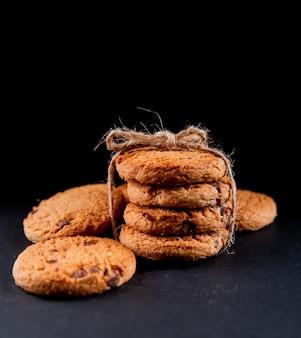 Вид спереди овсяное печенье с шоколадом на черном фоне
