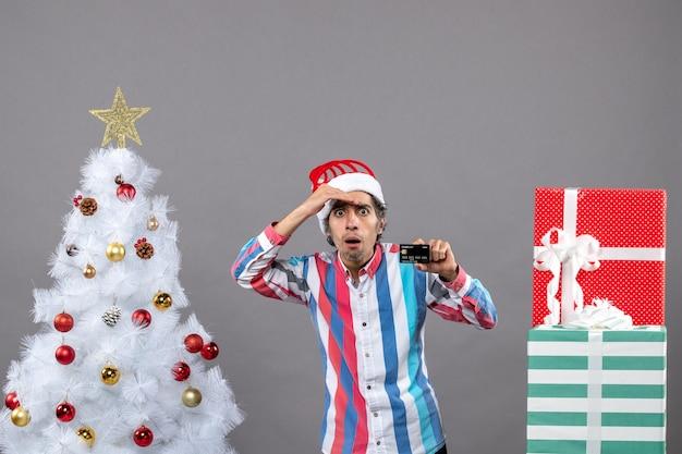 Вид спереди, наблюдающий за человеком, положившим руку на лоб, стоящим возле белой рождественской елки