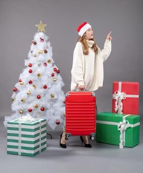 Вид спереди, наблюдающая за рождественской девушкой в шляпе санта-клауса, держащей свою дорожную сумку возле белой рождественской елки