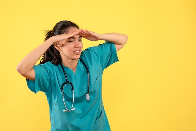 Vista frontale osservando il giovane medico femminile su sfondo giallo