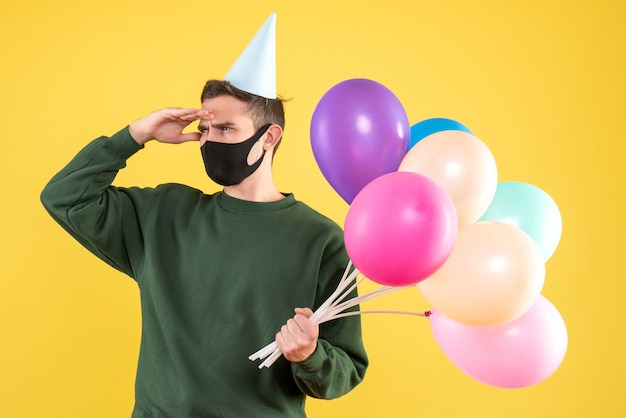 黄色の背景に立っているパーティーキャップとカラフルな風船を持つ若い男を観察正面図