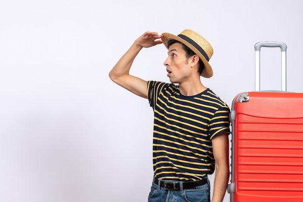 Front view observing young man with straw hat standing near red suitcase