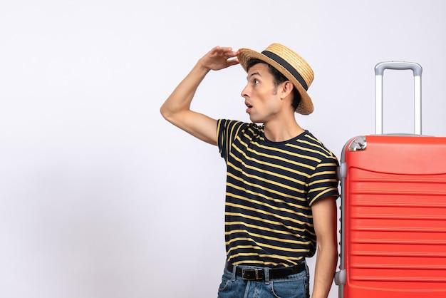 赤いスーツケースの近くに立っている麦わら帽子を持つ若い男を観察する正面図
