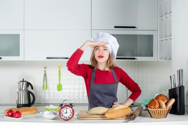 キッチンで料理の帽子とエプロンで若い女性を観察する正面図