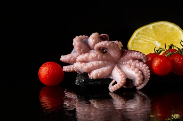 Front view octopus with lemon and tomatoes