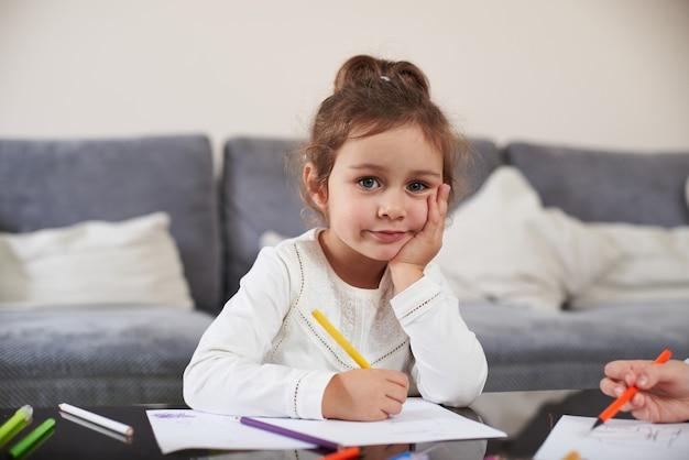 펜을 들고 카메라를보고 아름 다운 여자의 전면 모습. 집에서 공부하는 개념. 유치원 여자의 초상화