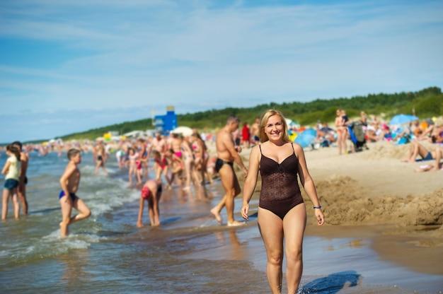 갈색 수영복을 입고 발트해를 따라 해변을 따라 걷는 아름다운 소녀의 전면 전망.