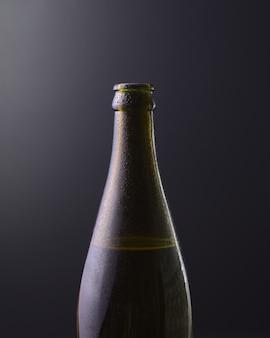 Вид спереди бутылки холодного пива с темно-черным фоном с фиолетовыми цветами градиента. холодные алкогольные напитки, концепция международного дня пива.