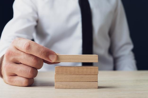 概念的なイメージで空白の木製のペグを積み重ねるビジネスマンの正面図。
