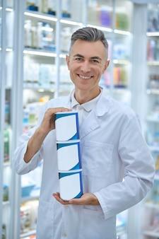 栄養補助食品と瓶を保持している白いローブで陽気な白髪の薬局の労働者の正面図