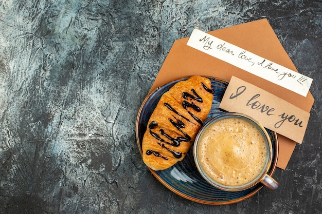 暗い表面に愛する人のための一杯のコーヒーと新鮮なおいしいクロワッサンの正面図