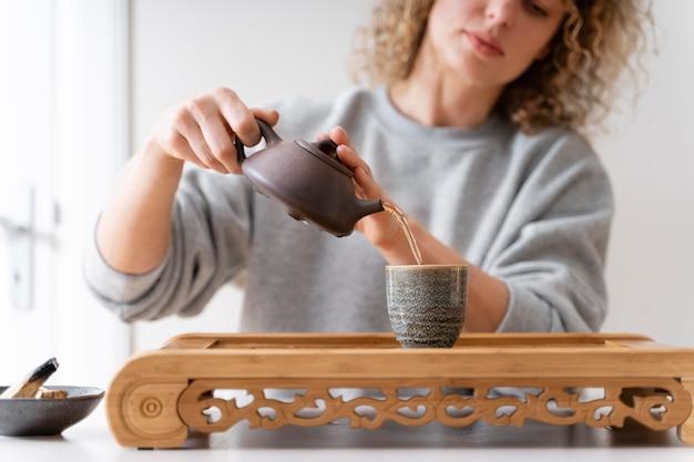 Вид спереди кудрявой блондинки, пьющей чай и расслабляющейся