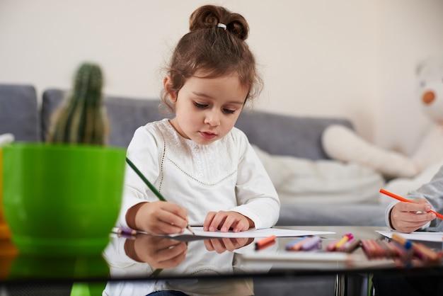 Вид спереди симпатичной девушки в белой рубашке, сосредоточенной на рисовании цветным карандашом. цветные деревянные карандаши, лежащие на столе.