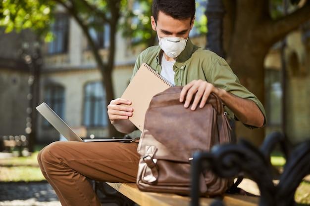 Вид спереди темноволосого парня в маске, сидящего на деревянной скамейке