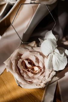 Вид спереди тусклой розовой розы на солнечных лучах и драгоценных обручальных кольцах