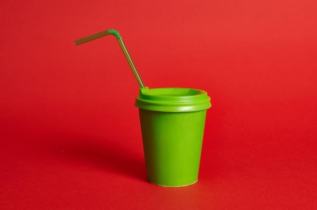 Вид спереди зеленой перерабатываемой картонной чашки с соломинкой на красном фоне. скопируйте пространство. цветовой контраст