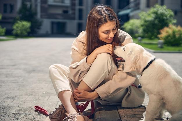 彼女のかわいい犬の横に足を組んで座っている幸せな長い髪の白人女性の正面図