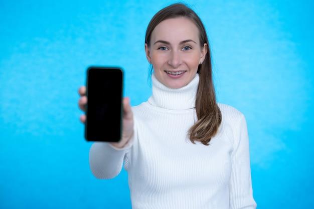 Вид спереди счастливой женщины, показывающей пустой дисплей смартфона