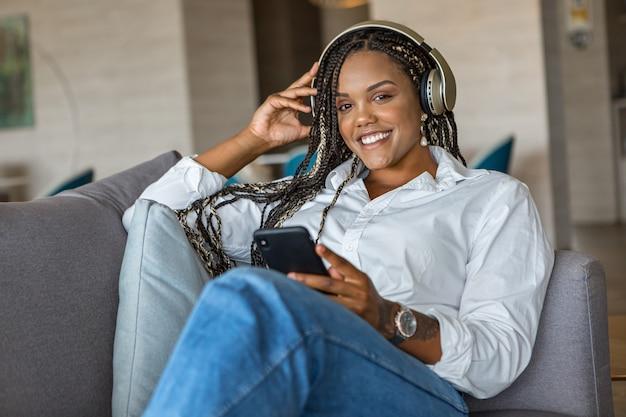 ヘッドフォンで音楽を聴き、カメラを見ながら自宅のソファに寄りかかって携帯電話を使用して幸せな若い女性の正面図。家の人々の概念。