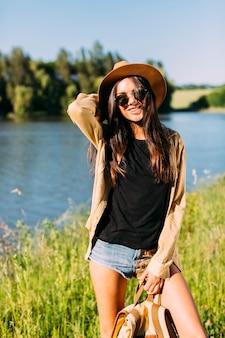 Вид спереди счастливая молодая женщина, создавая возле реки