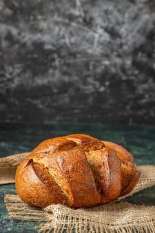 空きスペースのある暗い色の表面に茶色のタオルの上に食事の黒いパンの塊の正面図