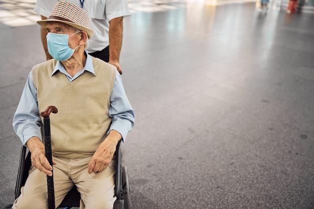 車椅子に座っている彼の手に杖を持っている男の正面図