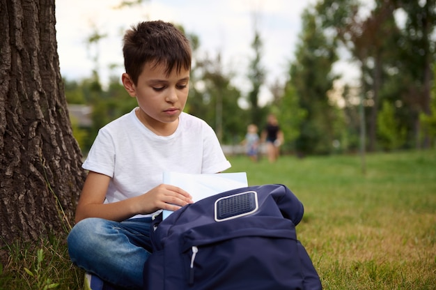 思春期前の男子生徒がバックパックからワークブックを取り出し、都市公園の緑の芝生に座って、屋外で宿題をする準備ができている様子の正面図。野外で学校の仕事をしている愛らしい子供