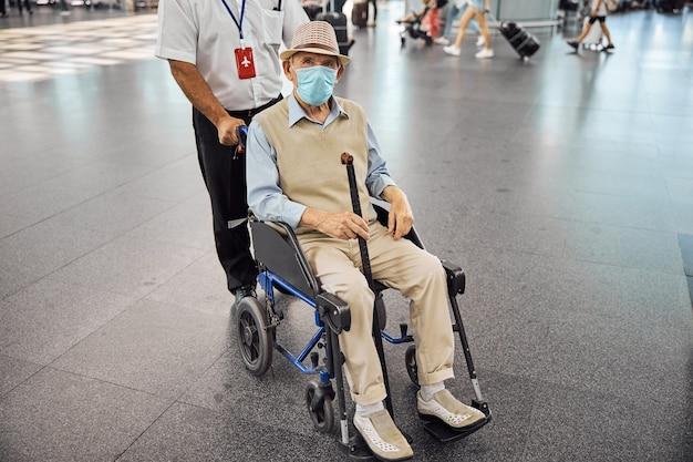 공항 터미널에서 휠체어에 앉아 수석 백인 남자의 전면보기