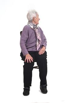 Вид спереди пожилой женщины, сидящей на стуле и оглядывающейся на белый фон