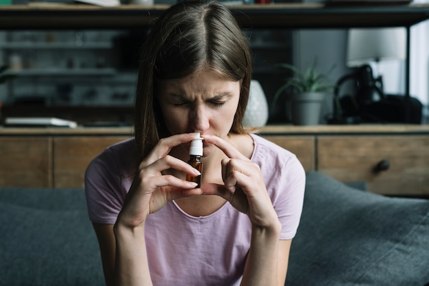 Вид спереди больной женщины, обнюхивающей носовой спрей