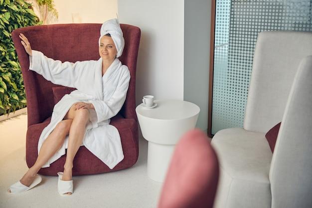 안락 의자에서 편안한 목욕 가운에 웃는 매력적인 아가씨의 전면보기
