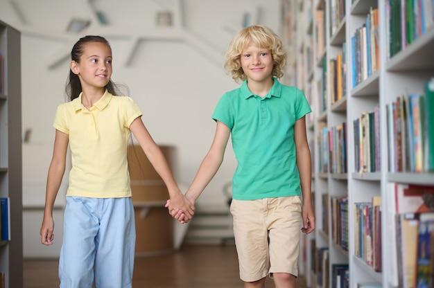웃는 귀여운 금발 남학생과 함께 걷는 예쁜 검은 머리 여학생의 전면 모습