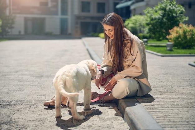 ペットの前の縁石に座っている笑顔の女性の正面図