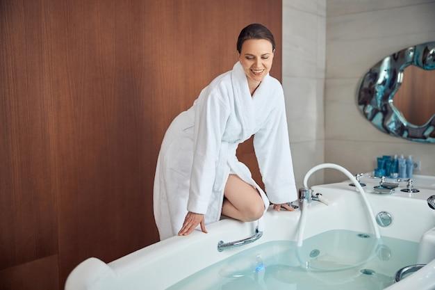 Вид спереди улыбающейся довольной темноволосой молодой кавказской женщины, смотрящей на воду в ванне