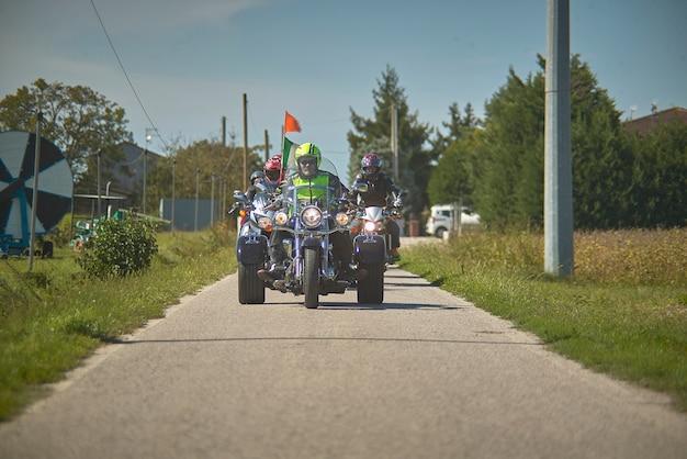 モーターサイクリストのチームを伴った、射撃地点に来る道路上のトライクの正面図。