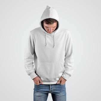頭を下げた若い男の白いパーカーのモックアップの正面図。店頭でのプレゼンテーション用のカジュアルな服のテンプレート。