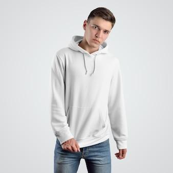 若い男のための白いパーカーのモックアップテンプレートの正面図。洋服のデザインスペース。店頭でのプレゼンテーション用の服。